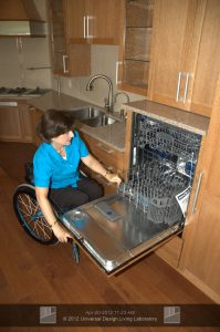 woman in wheelchair opening a dishwasher